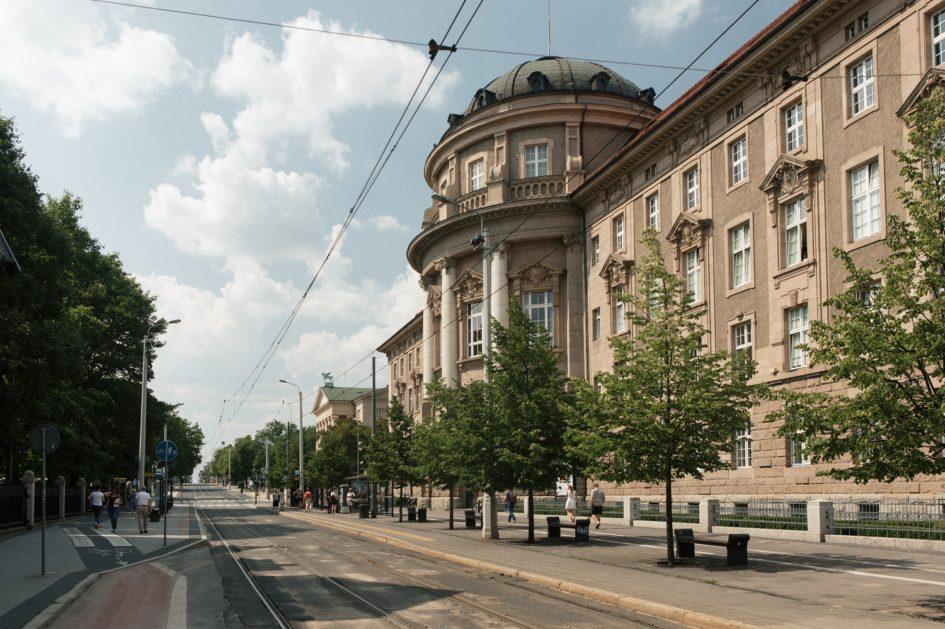 zabytkowy budynek w centrum miasta otoczony drzewami w sąsiedztwie przystanku autobusowego