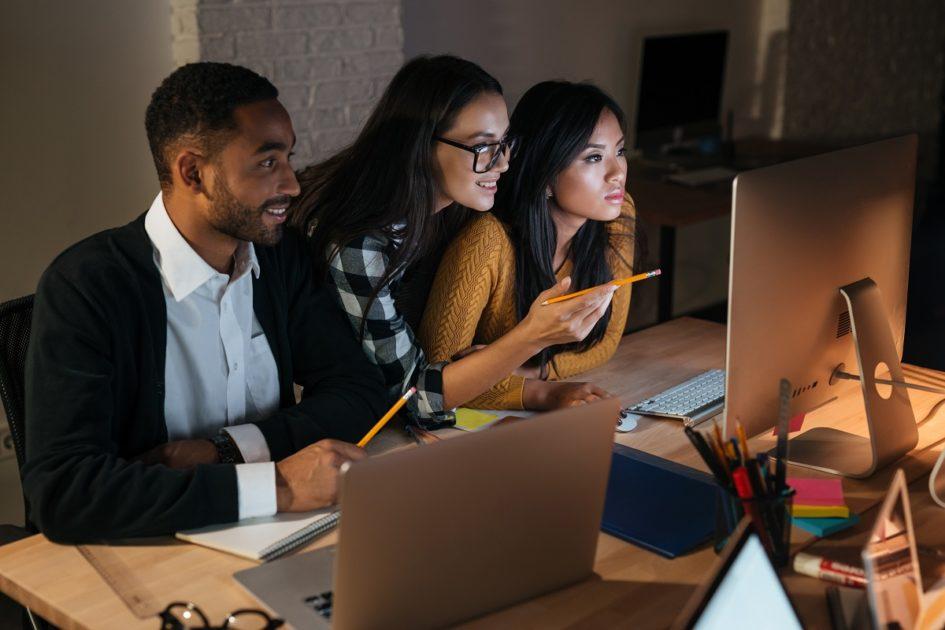 Młody mężczyzna i dwie dziewczyny przed siedzą przed dwoma komputerami. W dłoniach trzymają ołówki