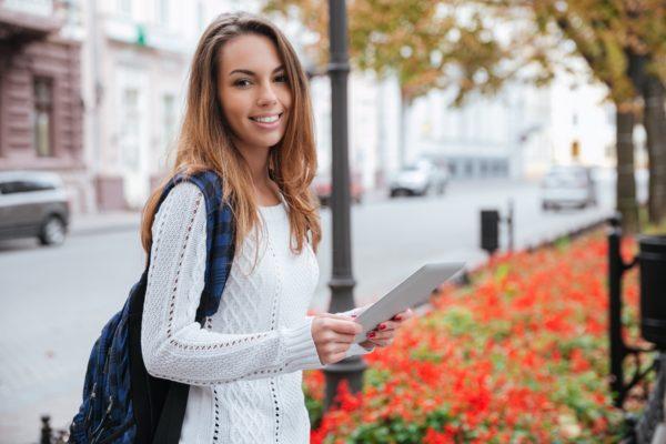 Młoda uśmiechnięta dziewczyna w jasnym swetrze i długich włosach z ciemnym plecakiem stoi przy spokojnej ulicy z tabletem w dłoniach. Znajduje się w mieście, przy skwerze obsadzonym czerwonymi kwiatami.