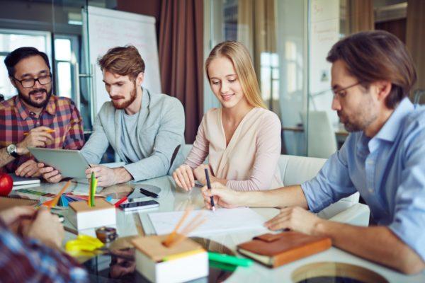 Grupa czterech młodych osób: trzech mężczyzn i jedna kobieta siedzą przy stole pełnym ksiązek, zeszytów i notatek. W tle tablica clickboard