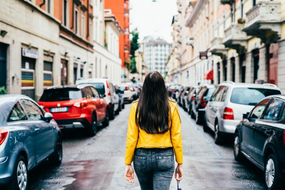 Brunetka w żółtej bluzie odwrócona tyłem idzie wzdłuż ulicy oparkowanej autami. Po obu stronach rozciągają się wysokie kamienice.