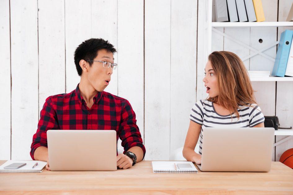 Dwoje młodych ludzi siedzi przy stole. Chłopak w koszulki w kratę i dziewczyna w bluzce w paski spoglądają na siebie z wyrazem zaskoczenia. Przed sobą mają komputery. Za nimi jasne tło.
