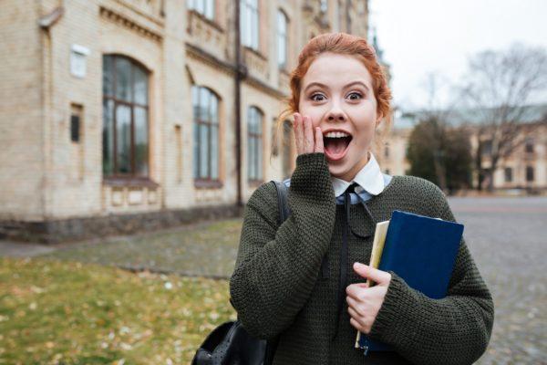 Młoda dziewczyna z książkami w dłoni stoi na tle kampusu z miną zachwytu