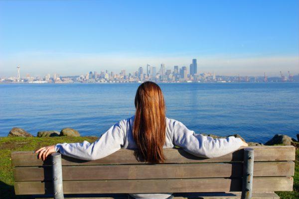 Na tle oceanu i odległego miasta odwrócona tylem dziewczyna siedzi na łąwce