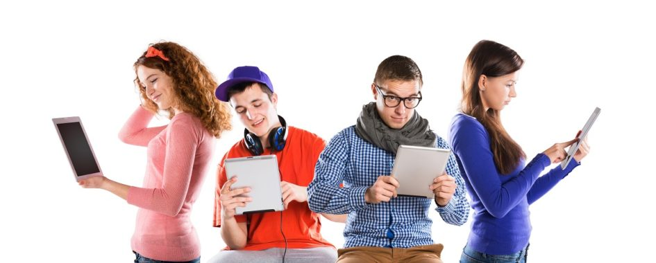 Czworo młodych ludzi stoi do siebie bokiem i oglądają film na tablecie