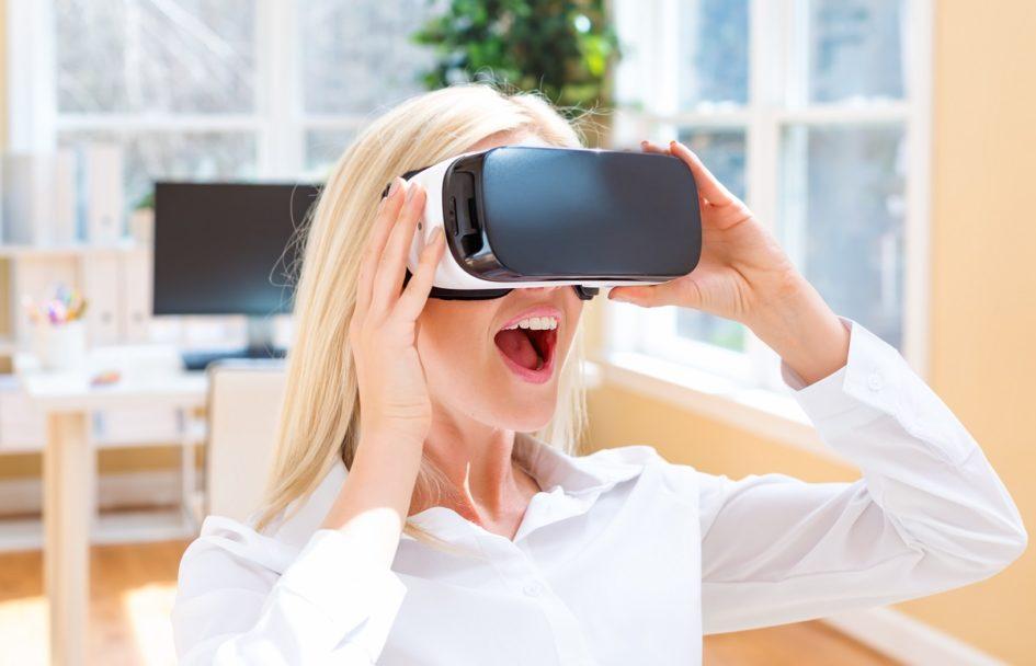 Młoda dziewczyna w biurze gra w grę cyfrową przy użyciu specjalnych okularów