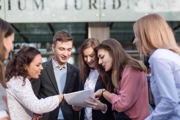 Grupa studentów przed wydziałem budynku analizuje dokument trzymany przez studenta w garniturze