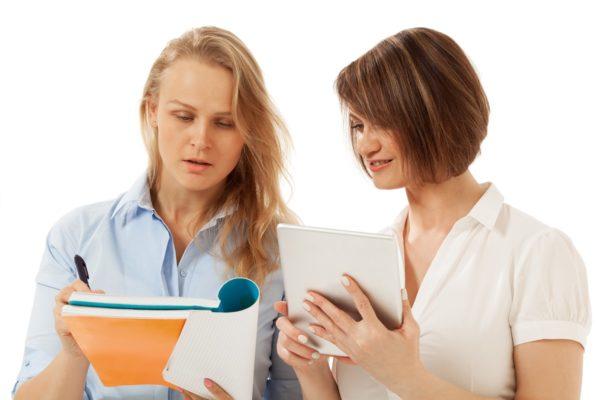 Dwie studentki z notatnikami w dłoniach wymieniają poglądy