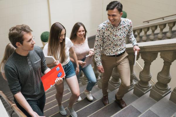 Grupa studentów z teczkami wchodzi do biblioteki