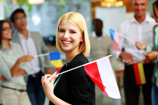 Młoda dziewczyna z flagą Polski w towarzystwie grupy osób
