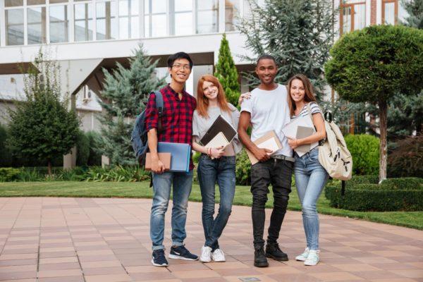 Czworo studentów na kampusie przed siedzibą uczelni