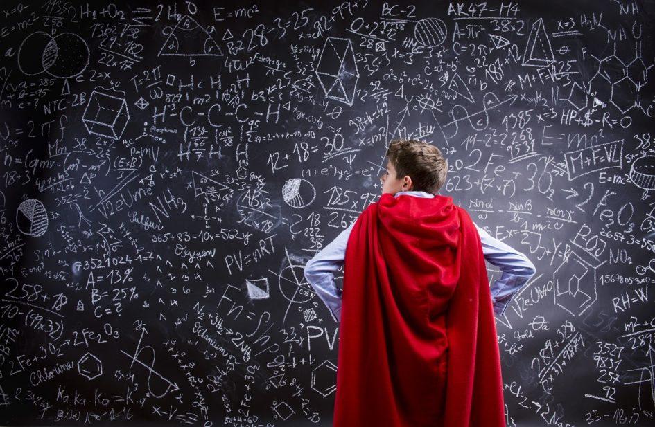 Młody mężczyzna w pelerynie bohatera stoi przodem do tablicy zapisanej równaniami