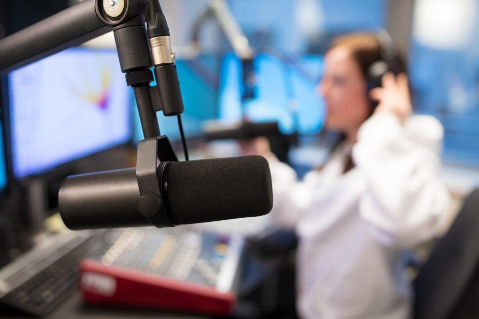Młoda dziewczyna w słuchawkach siedzi przed konsolą w studiu nagrań