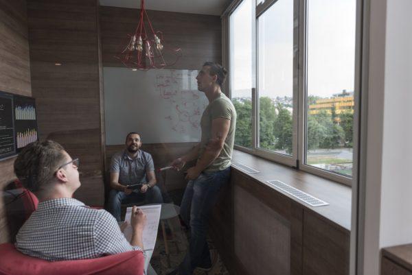 Informatyka na UAM. Trzech młodych mężczyzn przy tablicy