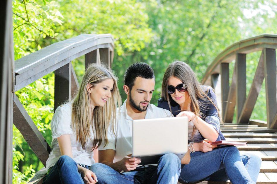Trzy młode osoby siedzą na mostku. Młody chłopak trzyma na kolanach komputer. Dwie dziewczyny patrzą na ekran